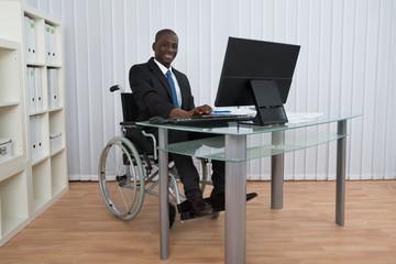 Businessman Working In Office Sitting On Wheelchair