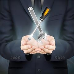 businessman holding tools set