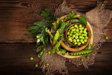 Fresh organic green peas on a wooden background. Rustic style.