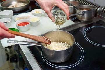 Chef is adding white wine to risotto