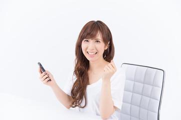 スマートフォンと喜ぶ若い日本人女性