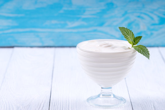 Fresh yogurt with mint in a bowl. White blue background.