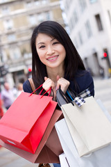 young chinese girl holding shopping bags