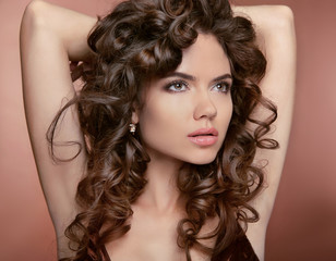 Wavy hair. Attractive girl with makeup. Curly hairstyle. Brunett