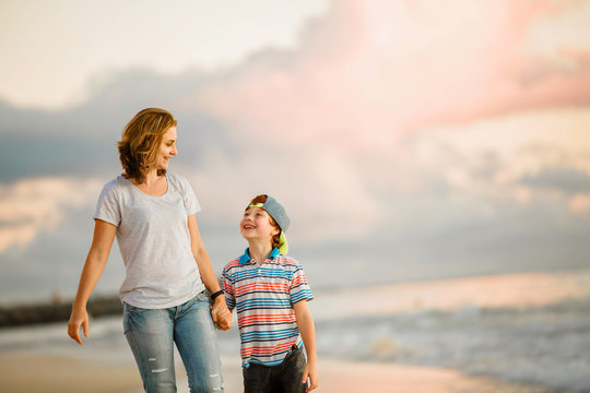 Young happy beautiful mother and her son having fun on the beach
