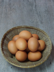 Fresh eggs in basket on wooden background