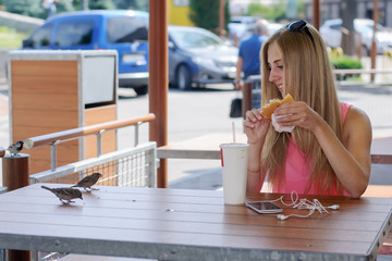 Girl sitting in cafe and feeding the birds