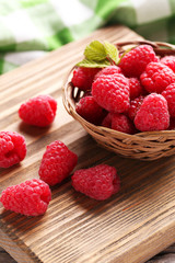 Red raspberries on cutting board on grey wooden background