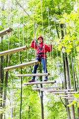 Kind passiert Hängebrücke im Klettergarten