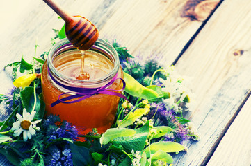 Honey in a glass jar with June flowers melliferous herbson a wooden surface. Honey with flowers