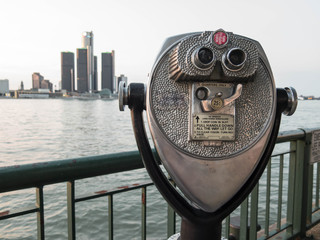 Detroit Sightseeing from Windsor. Sightseeing tourist binoculars overlooking downtown Detroit, Michigan on a summer afternoon from Windsor, Ontario, Canada.