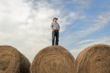 horizontal image of one farmer wearing a cowboy hat standing on a huge hay bale with his hands in his pockets gazing across the land under a beautiful cloud filled sky in the summer time