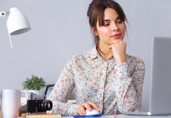 Portrait of  young woman sitting at  desk