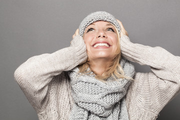 lovely young woman with blonde hair wearing winter hat and clothes, looking up with hands on ears for fun and happiness
