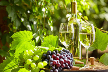 Wall Mural - Grape and white wine on wooden barrel on garden terrace