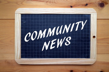 The phrase Community News in white text on a blackboard