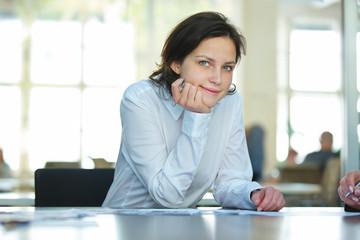Geschäftsfrau sitzt nachdenklich am Tisch