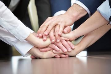Business Team stapelt Hände zur Motivation