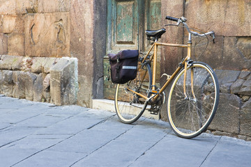 Yellow bicycle with bag against a stone wall
