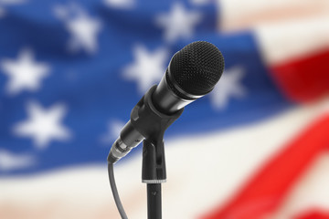 Microphone on stand with US flag on background