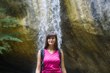 young caucasian female hiker near the waterfall