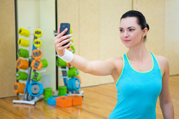 sporty woman making selfie photo on smartphone in gym