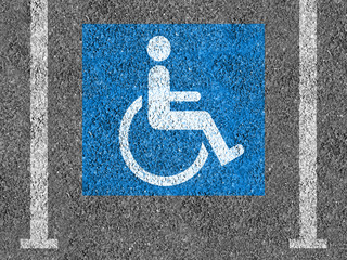 Blue and white Handicap parking symbol on asphalt