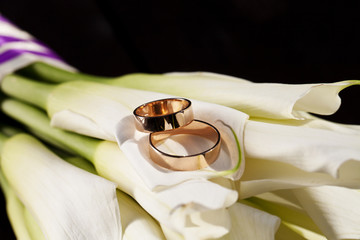 wedding rings and a bouquet of white lilies