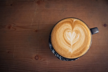 cup of coffee top view surface heart shape in wooden background