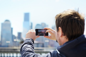 Tourist taking mobile photo of skyscrapers