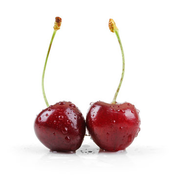 two wet cherries isolated on white