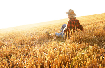 Senior farmer sitting in a wheat field after harvest and looks into the distance