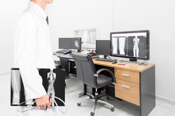 Doctor holding x-ray image with stethoscope in operating room