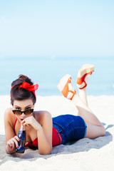 Pin-up on sand with drink