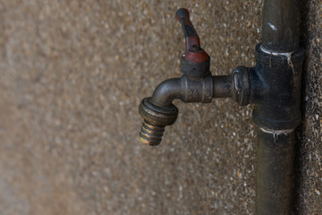 Old faucet beside,wall,