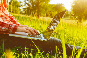 Hands using laptop and typing in summer grass