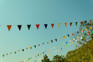 colorful festive bunting flags against a blue sky background