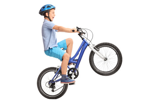 Little boy doing a wheelie on a small blue bike