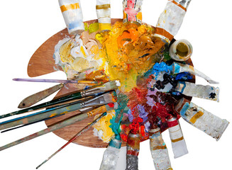 Artistic palette, oil paints, brushes and other art supplies isolated on white background