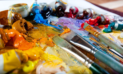 Art palette with oil paints and brushes. theme with paint brushes and palette