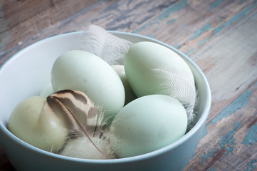 Fresh hens eggs in a bowl with some feathers. Served on a rustic wooden table.