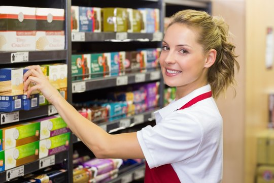 Portrait of a smiling worker taking a product in shelf