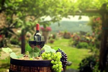 Obraz Czerwone wino z baryłką na baryłce wina w zielonej Toskanii, Włochy - fototapety do salonu