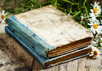 Old books, bouquet of field daisies on a wooden background in vi