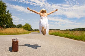Mädchen mit Koffer auf Feldweg