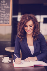 Young business woman sitting at the table and writing in a notebook. On table she has cup of coffee