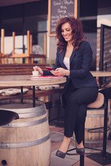Young business woman drinking coffee and use her smartphone