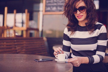 Beautiful young woman sitting in a cafe and mixes coffee with the spoon. On table she has her mobile phone ready to call her friends to join her