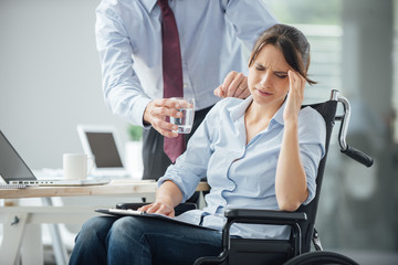 Disabled business woman with headache