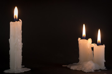 Three White Candles Burning at Night Time